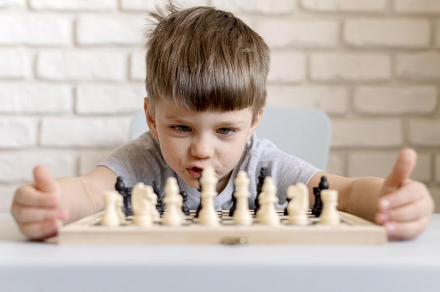 chłopiec patrzy na rozłożone szachy