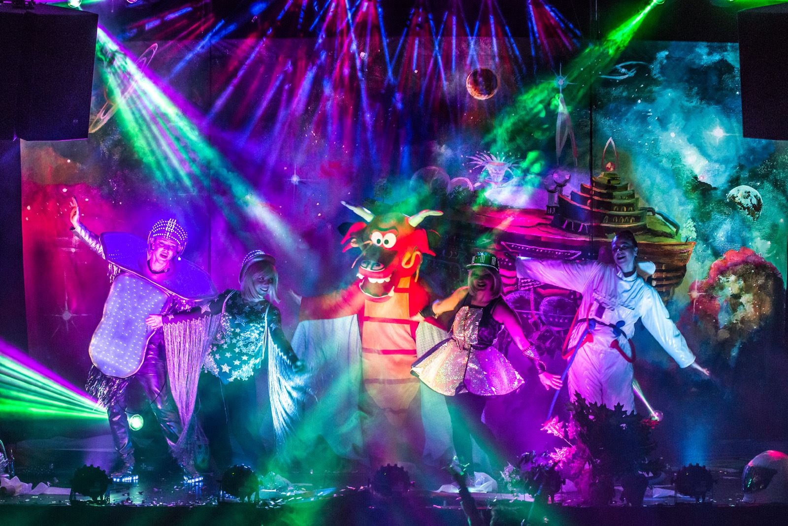 5 aktorów w kostiumach na scenie z dużą ilościa kolorowych swiateł
