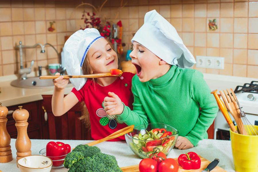 Szczęśliwa dwójka zabawnych dzieci przygotowuje w kuchni sałatkę ze świeżych warzyw