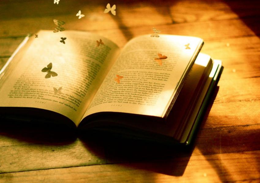 Książka lezy na stole i wylatują z niej papierowe motyle
