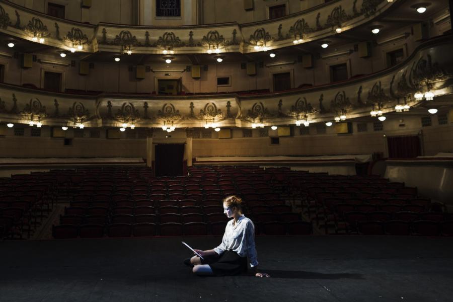 aktorka ubrana na biało z pomalowaną twarzą siedzi na scenie i czyta