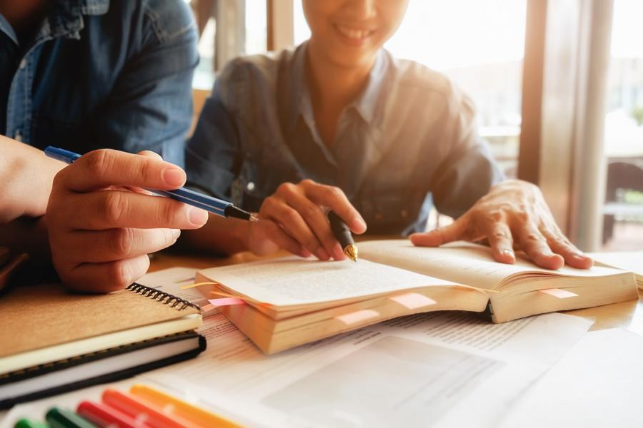 Koncepcja edukacji. Student studia i burza mózgów koncepcja kampusu. Zbliżenie na uczniów omawiających swój temat w książkach lub podręcznikach. Selektywne skupienie.