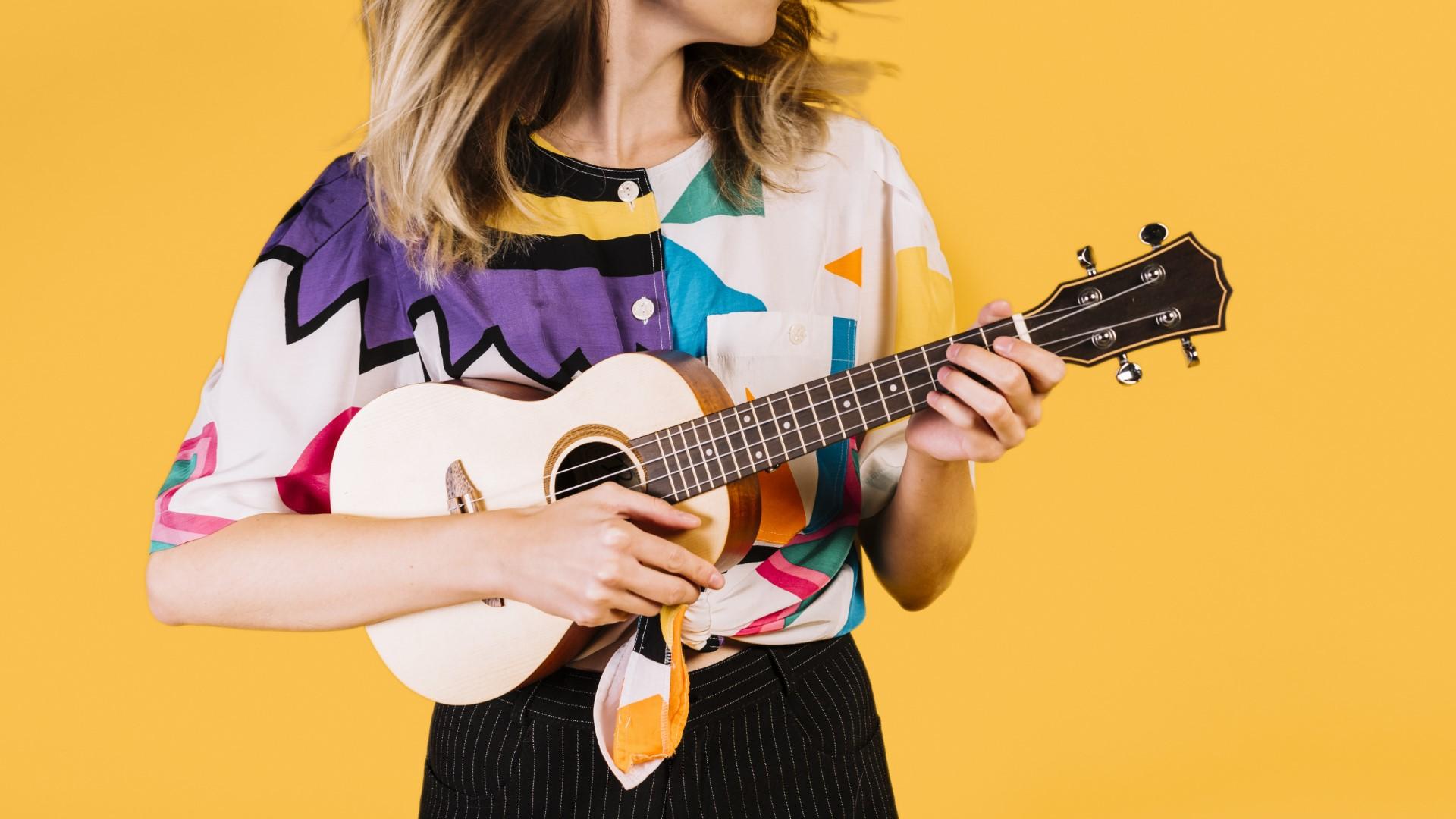 Kobiet gra na ukulele na żółtym tle