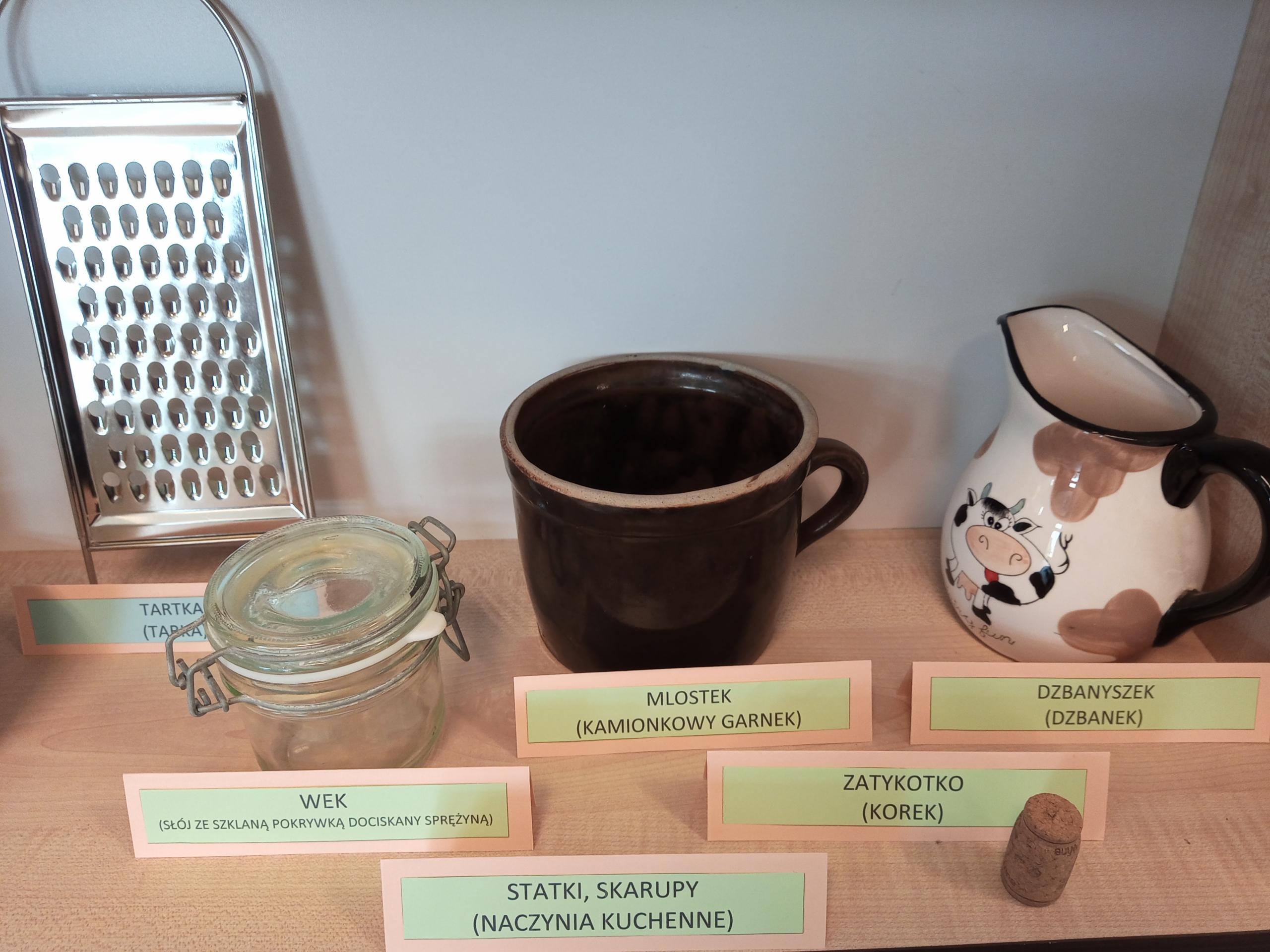 zdjęcie na którym widnieje tarka ręczna, dzbanek, mlostek, słój ze szklaną pokrywką i korek do wina