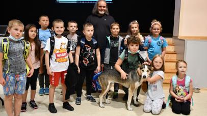 grupa dzieci z prowadzącym spotkanie i jego psem