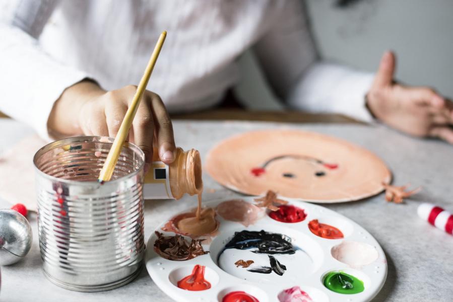 Dziecko maluje mikołaja na papierowym talerzyku