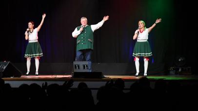 trójka wokalistów na scenie z rękoma podniesionymi do góry